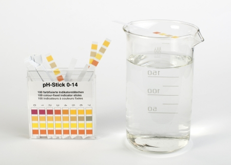 titration: Litmus strips for measurement of acidity.Beaker with water