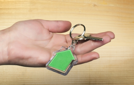 Keychain with figure of green house. Hand holding key and Keychain. photo