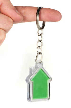 keychain: Keychain with figure of green house. Hand holding key and Keychain.