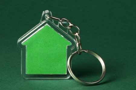 Keychain with figure of green house on green background photo