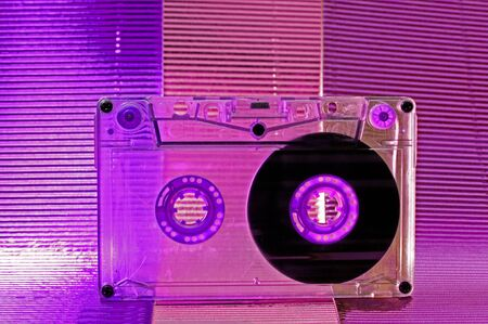 Transparent Cassette tape. Pink and blue background. photo