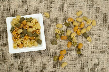 rotini: Multicolored pasta on burlap brown background