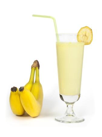Banaan milkshake en vers fruit banaan. Cocktail met melk. Witte geïsoleerde glas milkshake.