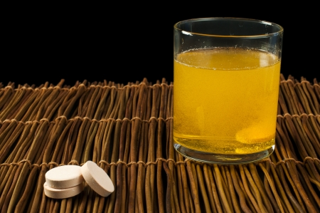 Vitamins pills soluble in water. Glass of water with vitamins. photo