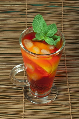 Ice tea with lemon. Glass ice tea with ice cubes and mint. photo