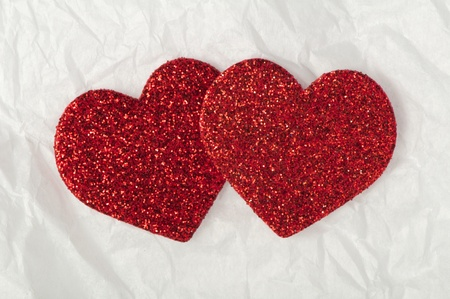Shiny red hearts on white crumpled paper photo