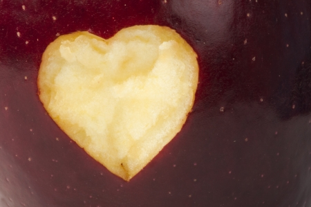 Heart shape closeup carved in red apple photo