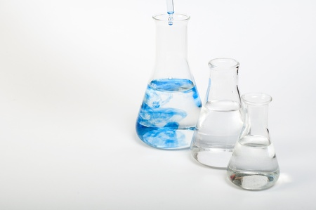 Laboratory equipment and color chemicals on white background Standard-Bild