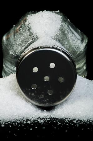 saltshaker: Pile of spilled salt and saltshaker black isolated Stock Photo