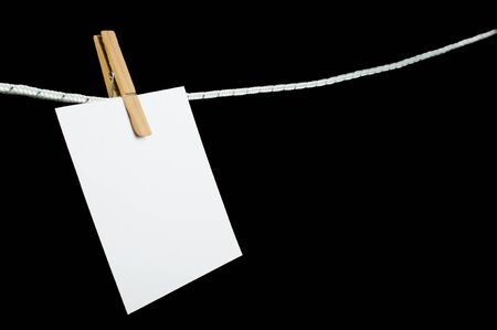 hooked: Note paper hooked on a rope. Balck isolated studio shot