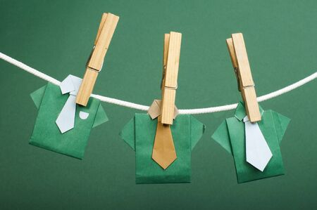 Origami shirts on rope. Green background photo