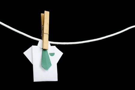 Origami shirt on rope. Black isolated photo
