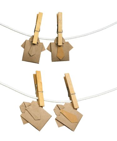 Origami brown shirts on rope. White isolated photo