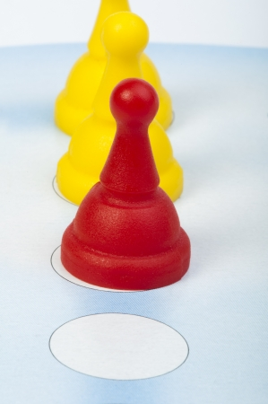 Red and yellow game pawns white isolated. Lideship conception Stock Photo - 18232467