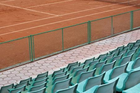grandstand: Green grandstand seats and tennis court