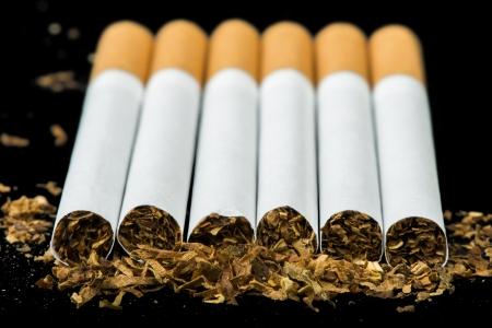 cigarrillos: Dispuestos en una fila de cigarrillos y tabaco esparcido Foto de archivo