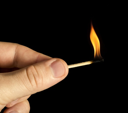 Hand holding burning match stick. Black isolated photo