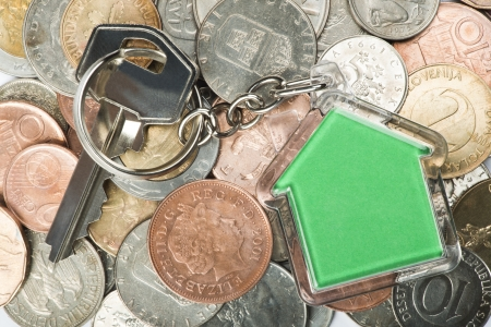Coins and green house key ring. White isolated studio shot photo