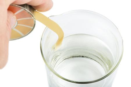 titration: Litmus paper and beaker  Hand holding litmus paper