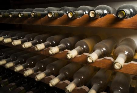 Wijnflessen op plank. Wijnkelder. Close-up wijnflessen.