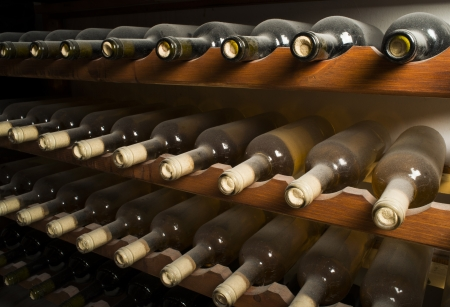 Wine bottles on shelf. Wine cellar. Close up wine bottles.