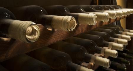 botella de licor: Botellas de vino en estante. Bodega. Cierre de botellas de vino.