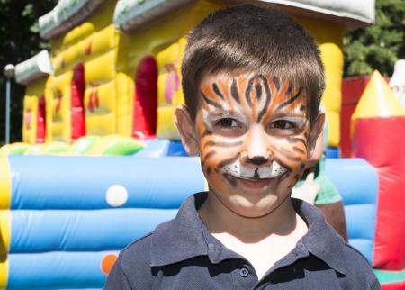 maquillaje infantil: Niño con la cara pintada. Pintura del tigre. Niño en fiestas para niños