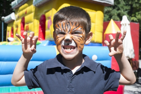 Child with painted face. Tiger paint. Boy on childrens holiday photo