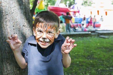 Child with painted face. Tiger paint. Boy on childrens holiday Stock Photo