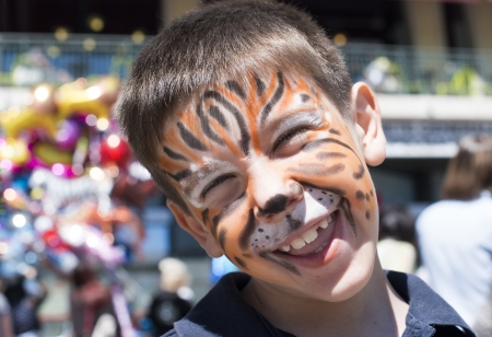 Child with painted face. Tiger paint. Boy on childrens holiday Zdjęcie Seryjne