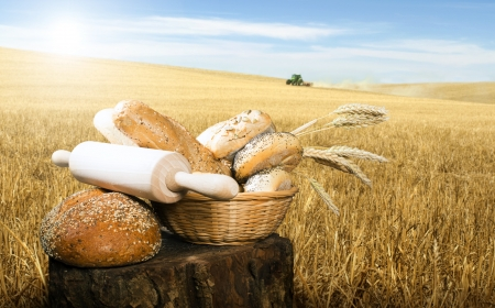 Bread,rolling pin and wheat cereal crops. Cereal crops on the background photo