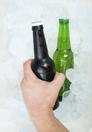 Hand holding bottle of beer and ice cubes photo