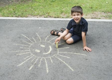 Child drawing sun on asphalt in a park photo