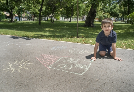 Child drawing sun and house on asphalt in a park photo