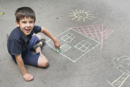 person outside: Child drawing sun and house on asphalt in a park