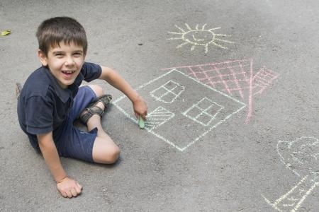 Kindtekening zon en huis op asfalt in een park