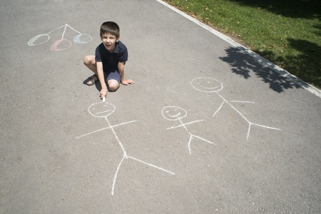 Child drawing family on asphalt in a park photo