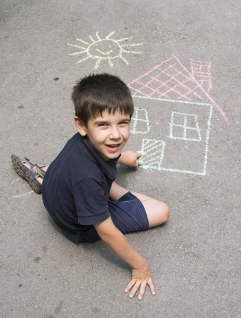 Child drawing sun and house on asphalt in a park