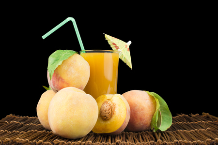 Peaches and glass with juice black isolated studio shot. Stock Photo - 22186316