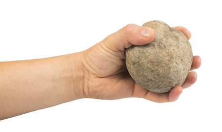 Hand holding stone ball. Piece of stone