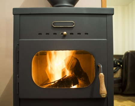 Wood stove and wood burning inside Stock Photo