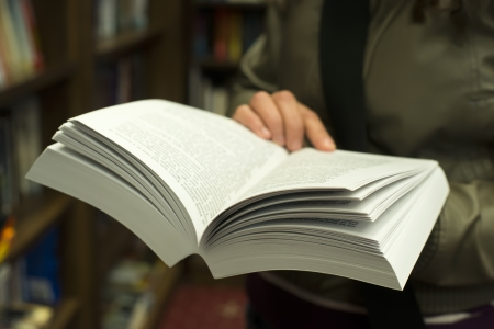 Hand holding open book in a bookstore.