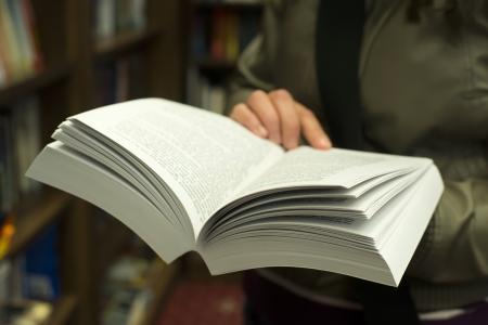 Hand houden van open boek in een boekhandel.
