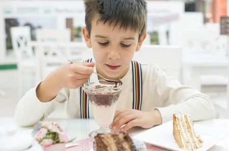 Child eat milk choco shake on a table photo