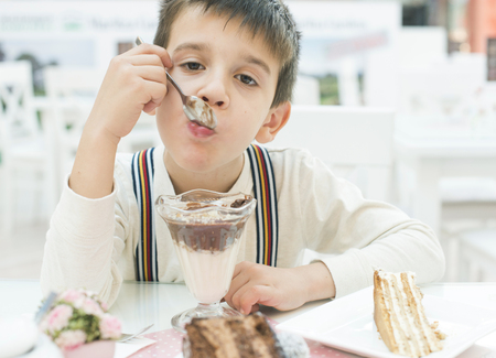 Child eat milk choco shake on a table photo
