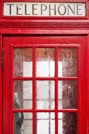 antique booth: Red Phone cabine in London. Vintage phone cabine monumental.Rainy day Stock Photo