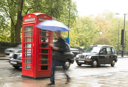 Red Phone cabine in London.  Man walking with umbrella Stock Photo - 24192525