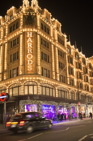 harrods: Harrods department store. Facade illuminated at night. Taxi passes in front of the building
