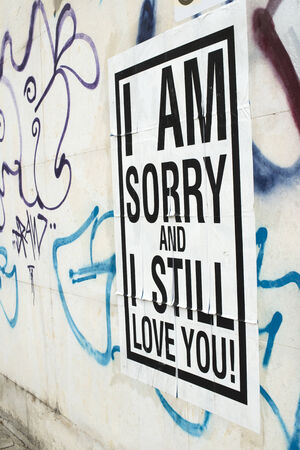 glued: Text poster glued to the wall. I amsorry and I stilllove You. Stock Photo