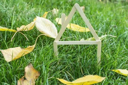 outumn: Model house made of wooden sticks on green grass